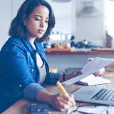 Mulher fazendo contas para impostos com calculadora e computador