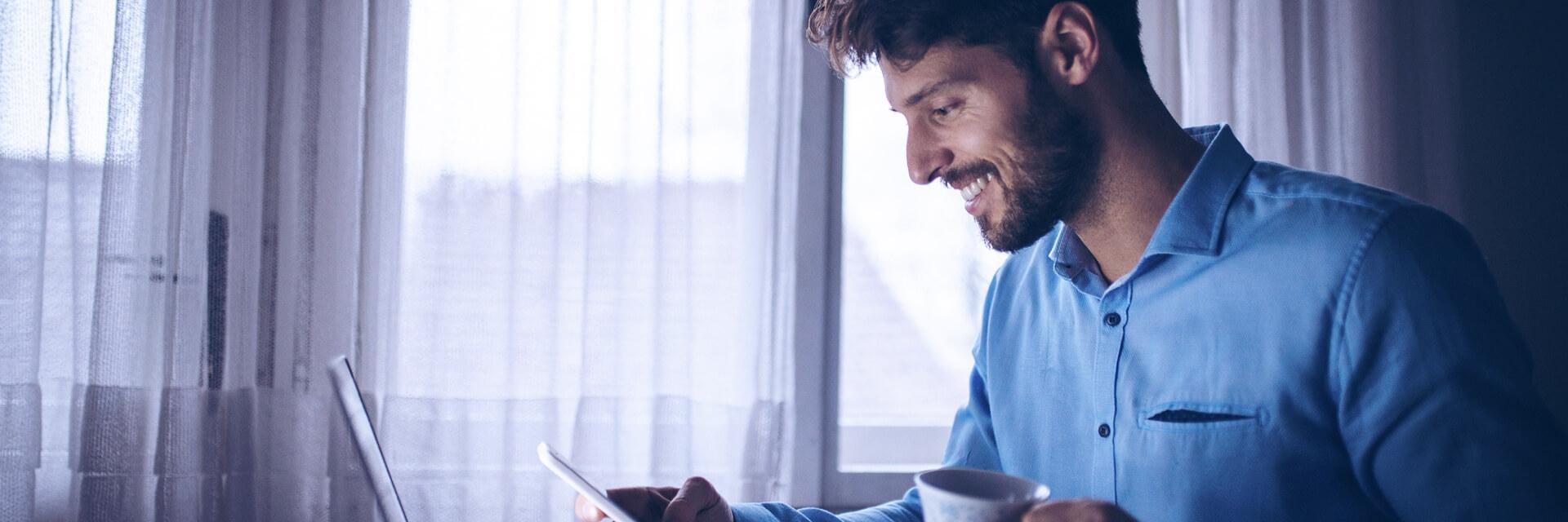 Homem usando computador e celular enquanto se serve de uma caneca