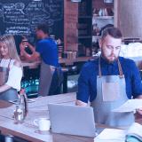 Homem conferindo documentos e computador no balcão de um café