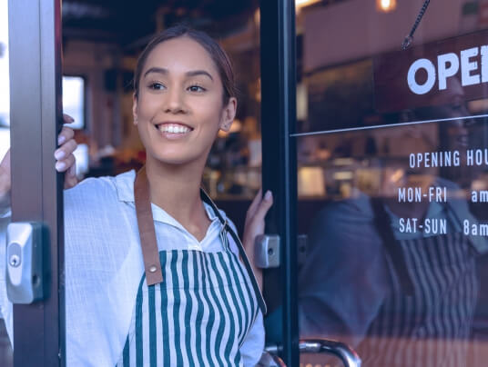 Mulher à frente de loja com porta aberta