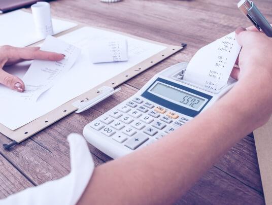 Empresária conferindo notas fiscais com a calculadora