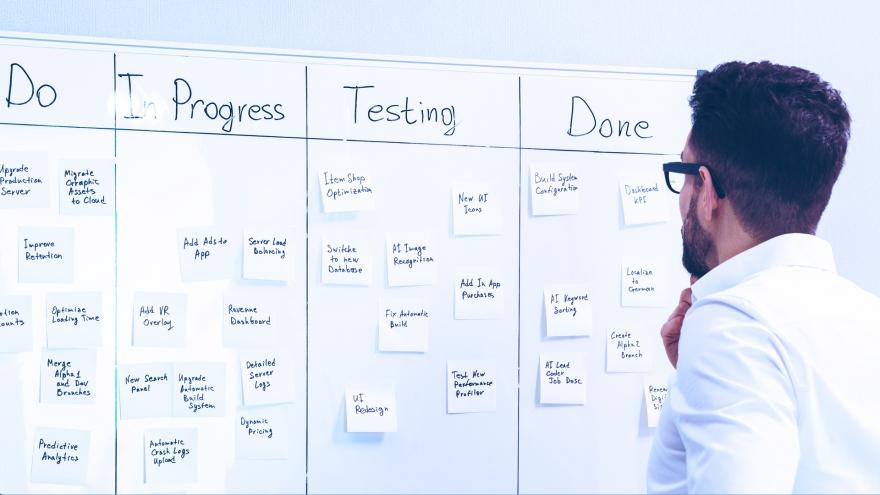 Homem analisando tarefas em quadro Scrum