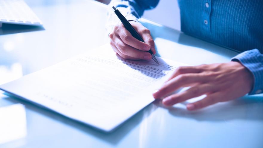 Homem escrevendo em um caderno sobre uma mesa