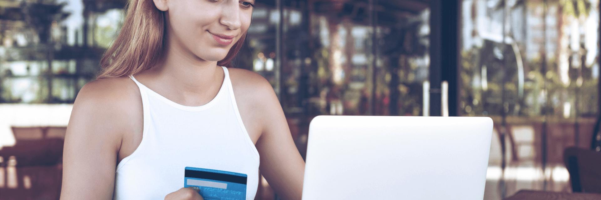 Mulher usando cartão de crédito em frente ao computador e sorrindo