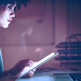 Mulher usando celular e notebook