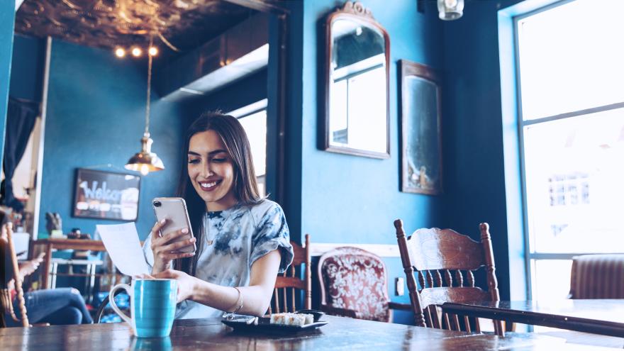 Mulher ao celular em um restaurante, pagando uma conta