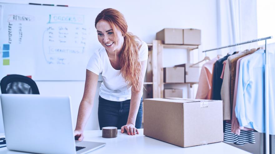 Mulher com computador organizando caixa para envio de compra online