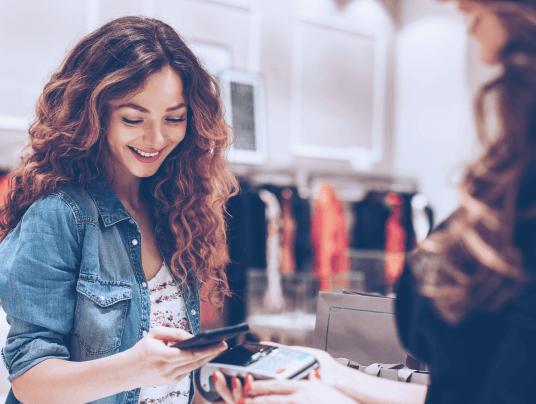 Mulher efetuando pagamento pelo celular em uma loja de roupas