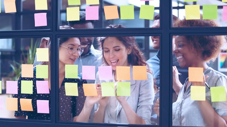 Mulheres discutindo conteúdo em frente a parede com post its