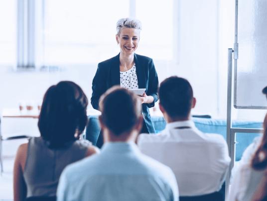 Cursos dentro da empresa com uma pessoa em frente dando aula e pessoas de costas olhando