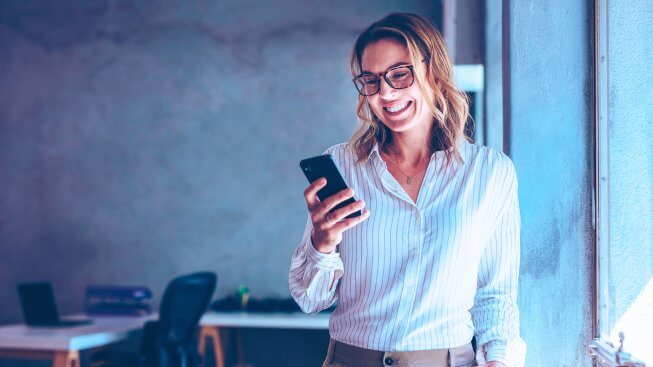 mulher-loira-de-oculos-segurando-celular-e-sorrindo